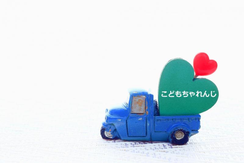 こどもちゃれんじを書かれた黒板を運ぶ青いトラック