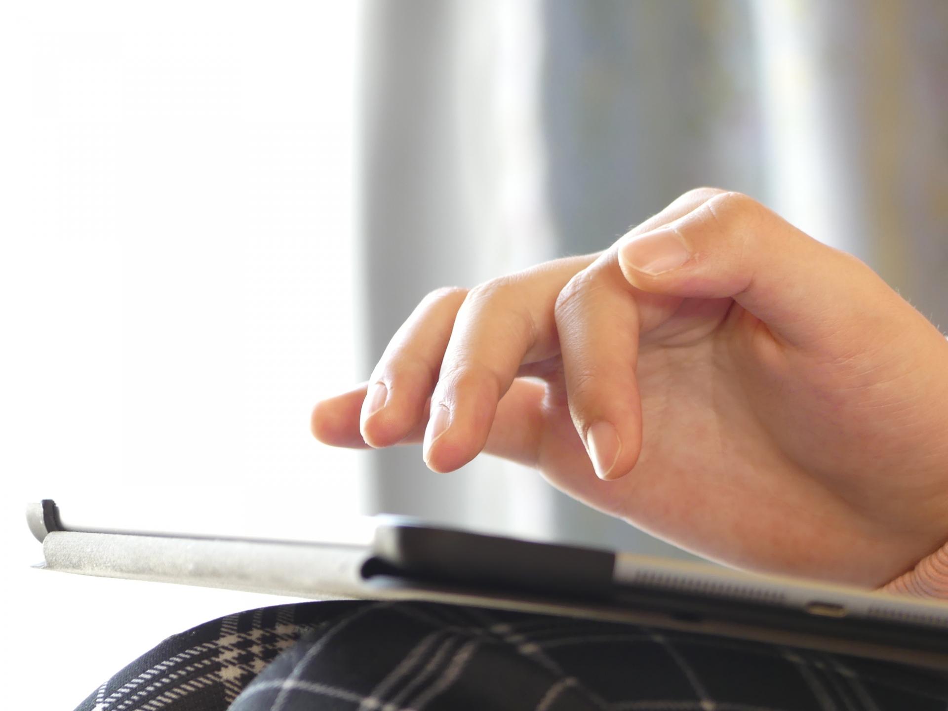 膝の上でタブレットと使う指