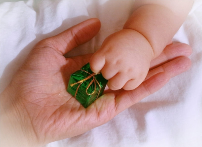 大人の手と赤ちゃんの手とプレゼント