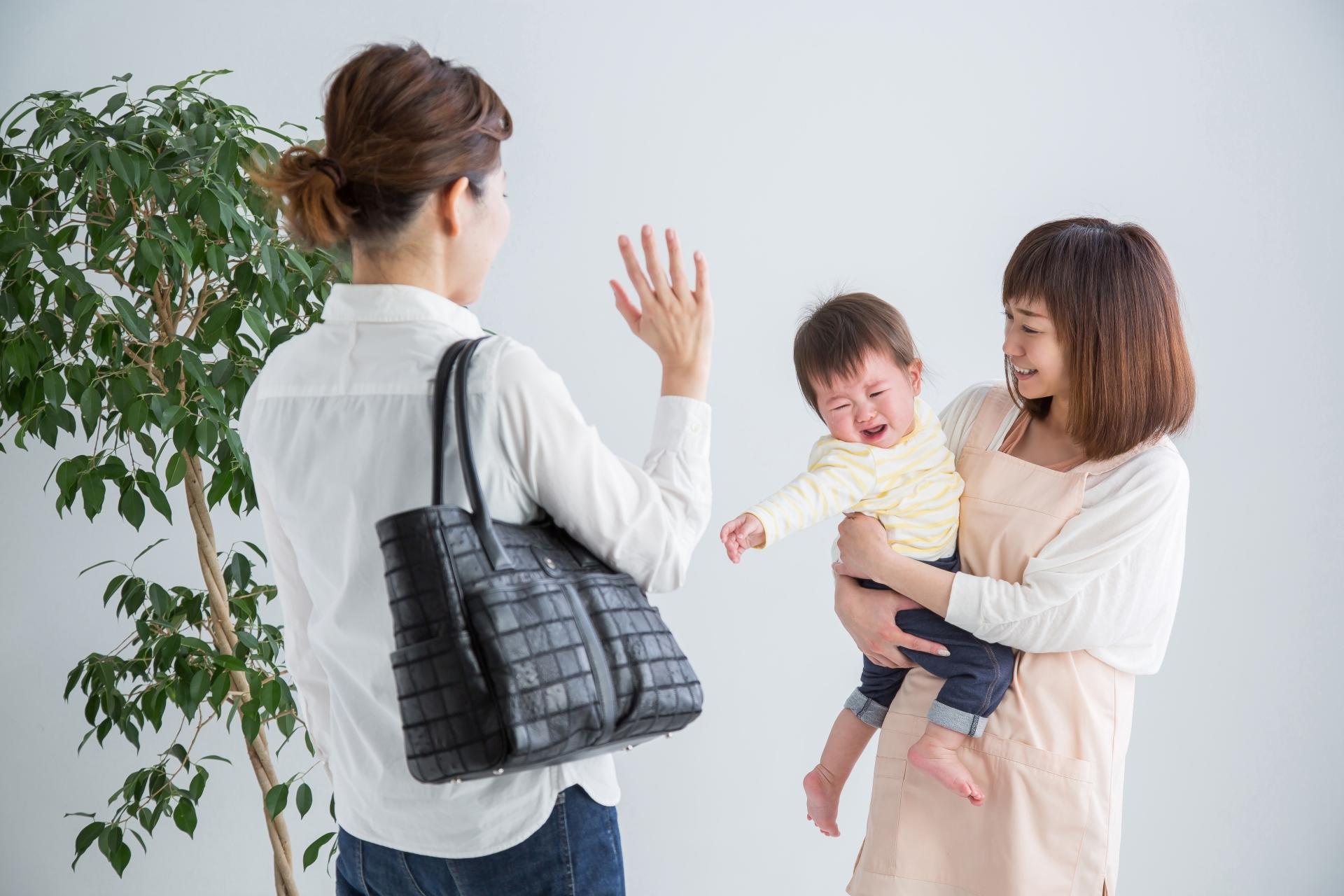 保育士に子どもを預ける女性