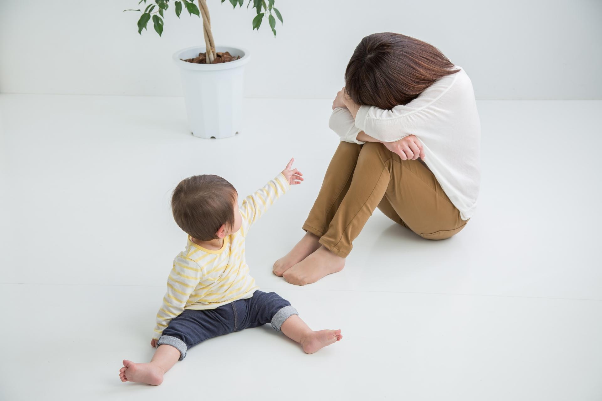 赤ちゃんと頭を抱える女性