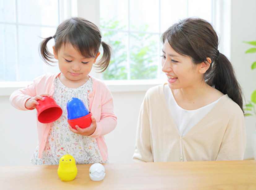カラフルなおもちゃで遊ぶ女の子とママ
