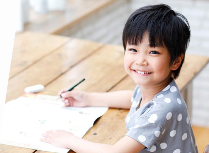 鉛筆を持つ笑顔の男の子