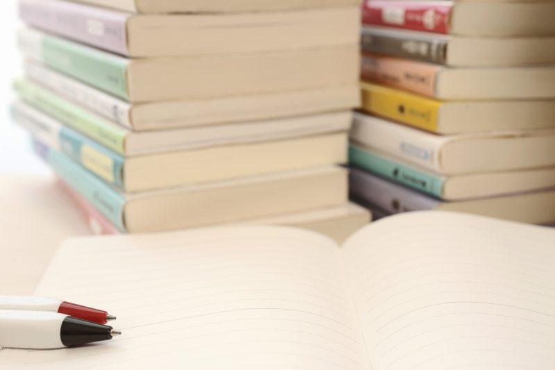 積み上げられた本とノート
