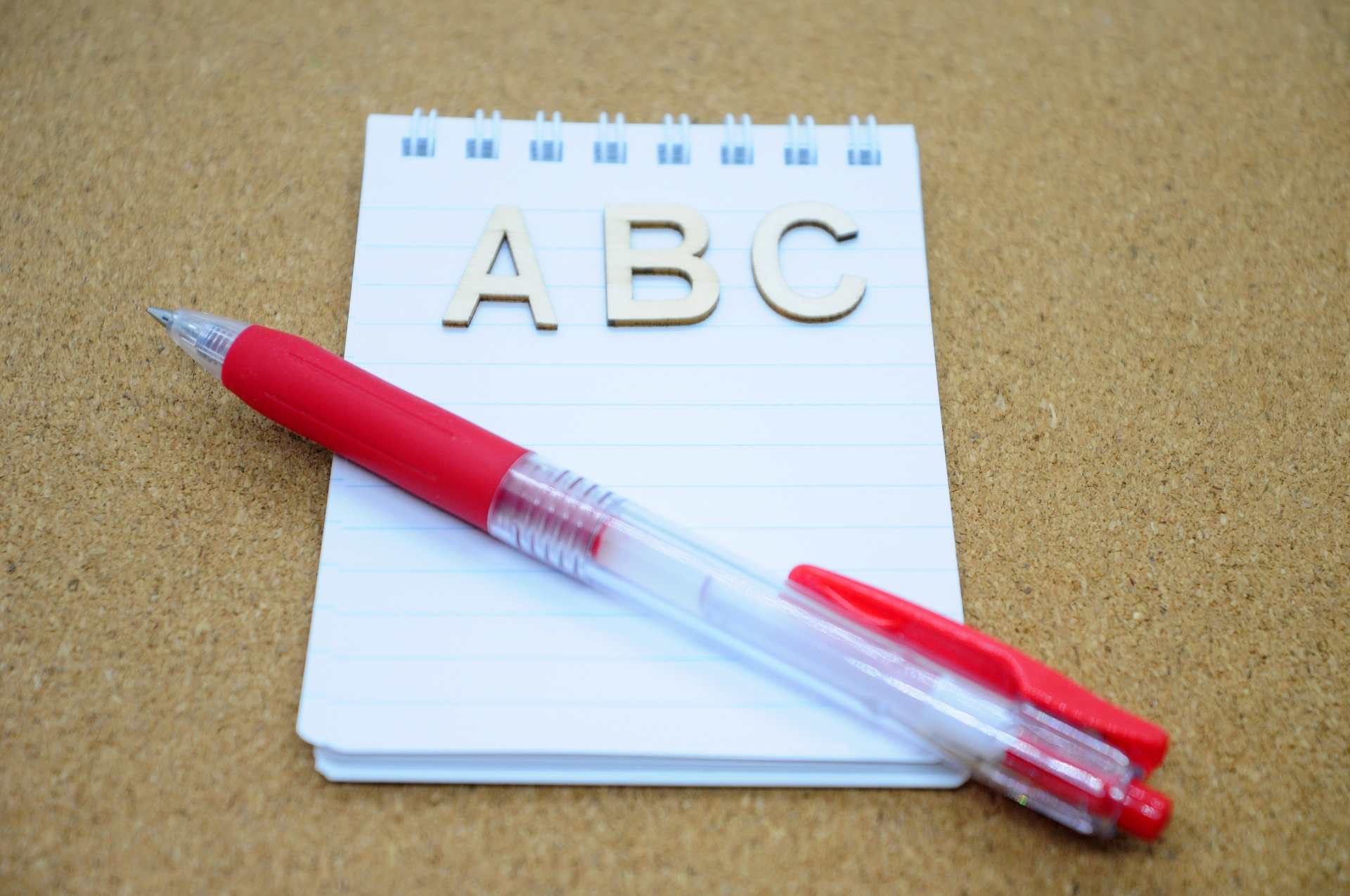 ABCと書かれたメモと赤いペン