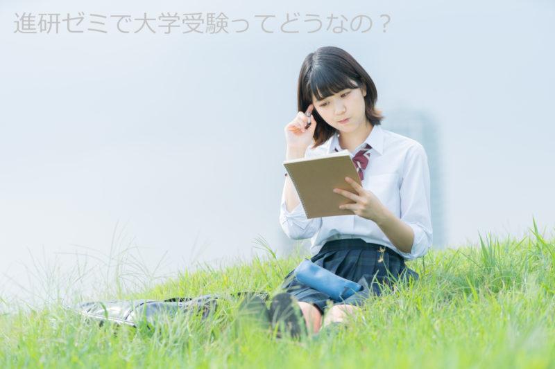 芝生に座って勉強する女子学生