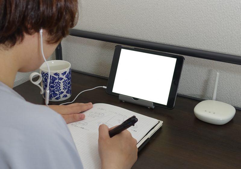 タブレットを見ながらノートに書き込む後ろ姿