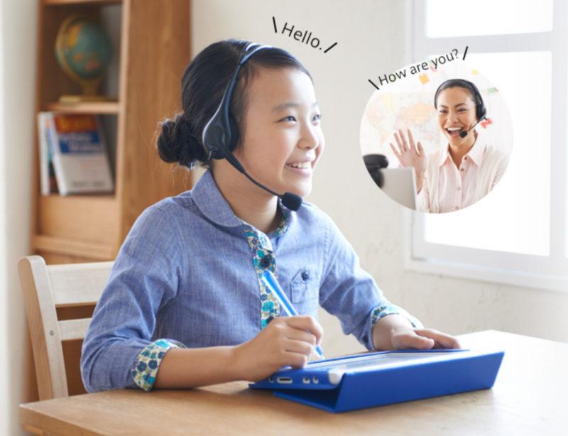 ヘッドフォンを付けてタブレットでオンラインで英会話をする女の子