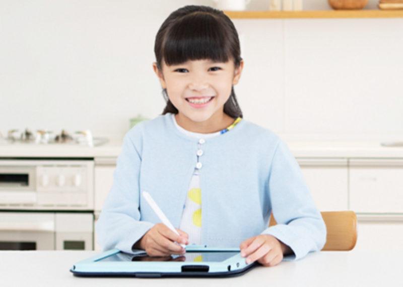タブレット学習をする笑顔の女の子