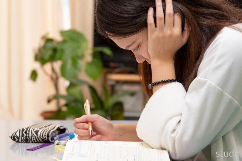 頬杖をつき勉強する女子