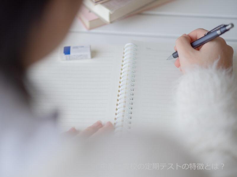 ペンを持つ後ろ姿とノートと消しゴム